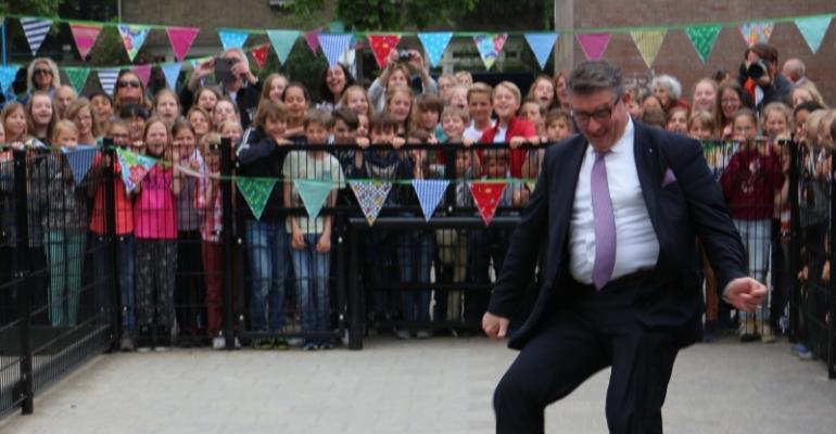 Onder luide aanmoediging van wel 300 kinderen legt wethouder Luca de bal voorzichtig voor zijn rechtervoet